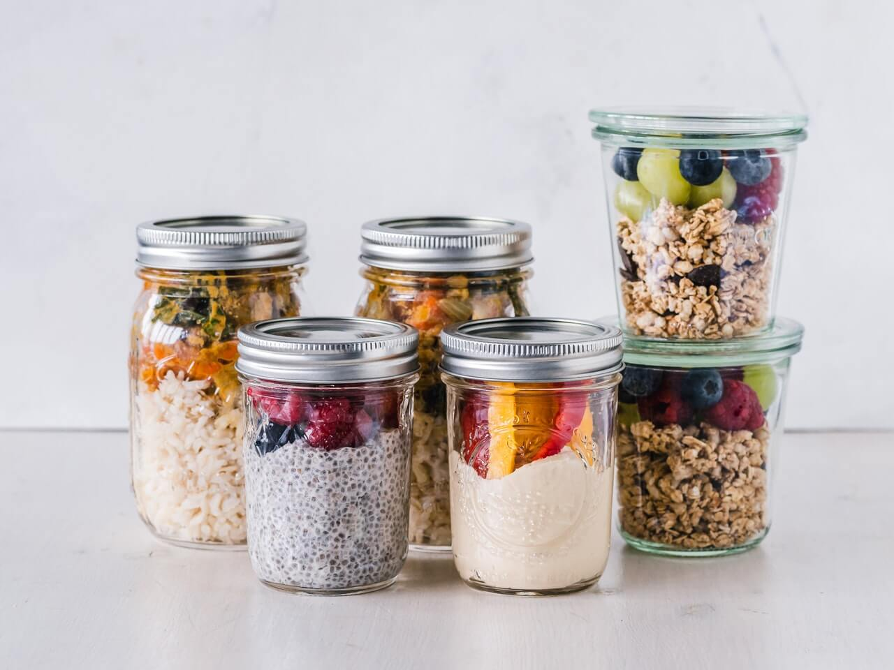 six-fruit-cereals-in-clear-glass-mason-jars-on-white-surface